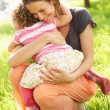 Stock Photo: Mother Cuddling Young Daughter In Summer Field