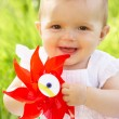 Baby Girl In Summer Dress Sitting In Field Holding Windmill - Foto de Stock