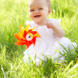 Baby Girl In Summer Dress Sitting In Field Holding Windmill - Stock Photo