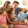 Parents Sitting With Children Reading Story Indoors - Stok fotoğraf