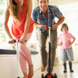 Parents Riding Childrens Scooters Whilst Son Looks On — Stock Photo