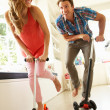 Stock Photo: Couple Riding Childrens Scooters Indoors