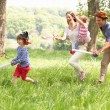 Parents Playing Exciting Adventure Game With Children In Summer - Stock Photo