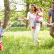 Parents Playing Exciting Adventure Game With Children In Summer - Stockfoto