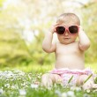 Baby Girl In Summer Dress Sitting In Field Wearing Sunglasses — Stock Photo #24441145
