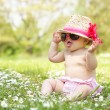 Baby Girl In Summer Dress Sitting In Field Wearing Sunglasses An - Foto Stock