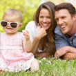 Parents With Baby Girl Sitting In Field Of Summer Flowers — Stock Photo