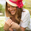 Stock Photo: Woman Lying In Field Of Summer Flowers With Straw Hat