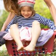 Stock Photo: Mother Carrying Son Sitting In Laundry Basket