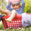 Young Boy Sitting In Laundry Basket - Stock Photo