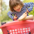 Young Boy Sitting In Laundry Basket - Stockfoto