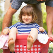 Father Carrying Son Sitting In Laundry Basket - Stockfoto