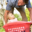 Father Carrying Baby Girl Sitting In Laundry Basket — Stock Photo