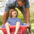 Father Carrying Son Sitting In Laundry Basket — Stock Photo