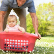 Father Carrying Baby Girl Sitting In Laundry Basket — Stock Photo #24441505
