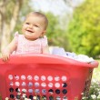 Baby Girl In Summer Dress Sitting In Laundry Basket - Lizenzfreies Foto