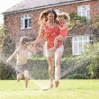 Mother And Two Children Running Through Garden Sprinkler — Stock Photo