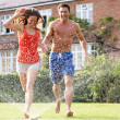 Couple Running Through Garden Sprinkler — Stock Photo