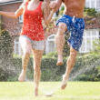 Stock Photo: Couple Running Through Garden Sprinkler