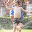 Father And Son Running Through Garden Sprinkler — Stock Photo