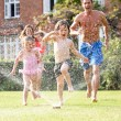 Family Running Through Garden Sprinkler — Stock Photo #24441713