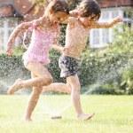 Two Children Running Through Garden Sprinkler — Stock Photo