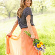 Stock Photo: Woman Walking Through Summer Field Carrying Bouquet Of Flowers