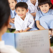 Foto de Stock  : Teacher Reading To Students In Chinese School Classroom