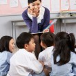 Foto Stock: Teacher Reading To Students In Chinese School Classroom