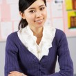Portrait Of Chinese Teacher Sitting At Desk In School Classroom - Stock Photo