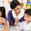 teacher helping students during art class in chinese school clas — Stock Photo #24442193