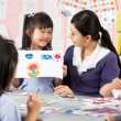 teacher helping students during art class in chinese school clas — Stock Photo #24442197