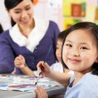 Female Pupil Enjoying Art Class In Chinese School Classroom — Stock Photo