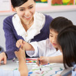 teacher helping students during art class in chinese school clas — Stock Photo #24442221