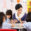 Teacher Helping Students During Art Class In Chinese School Clas — Stock Photo
