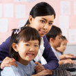 Teacher Helping Student During Computer Class In Chinese School — Stock Photo #24442329