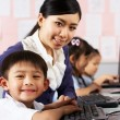 Teacher Helping Student During Computer Class In Chinese School — Stock Photo #24442331