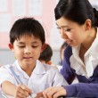 Teacher Helping Student Working At Desk In Chinese School Classr - Stock Photo