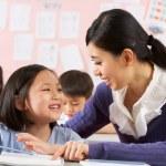 Profesor ayudando a estudiante que trabaja en el escritorio en escuela China classr — Foto de Stock