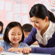 Teacher Helping Student Working At Desk In Chinese School Classr — Foto Stock