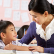 teacher helping student working at desk in chinese school classr — Stock Photo