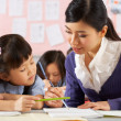 Stok fotoğraf: Teacher Helping Student Working At Desk In Chinese School Classr