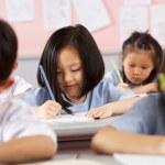 Grupo de estudiantes que trabajan en escritorios en aula escuela China — Foto de Stock