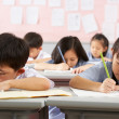 Group Of Students Working At Desks In Chinese School Classroom — ストック写真