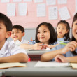 Стоковое фото: Group Of Students Working At Desks In Chinese School Classroom