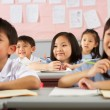 Stock Photo: Group Of Students Working At Desks In Chinese School Classroom