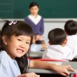 Portrait Of Female Pupil Working At Desk In Chinese School Class — 图库照片