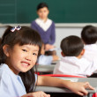 Portrait Of Female Pupil Working At Desk In Chinese School Class — Stock Photo #24442815