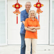 Senior Chinese Couple Outside Home Decorated With Welcoming Feng — Stock Photo #24443823
