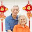 Senior Chinese Couple Outside Home Decorated With Welcoming Feng - Stock Photo